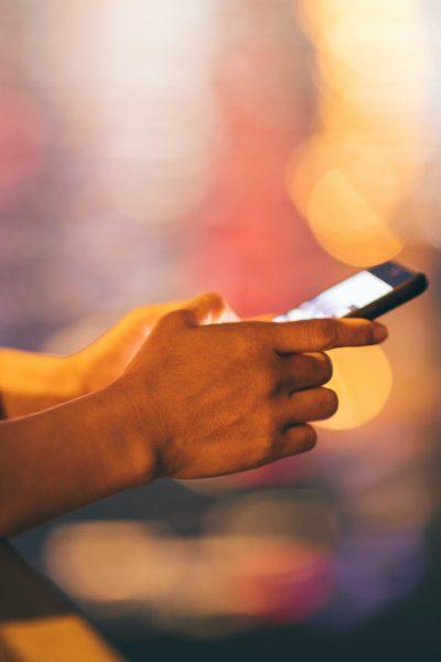 Hands using smartphone on night city